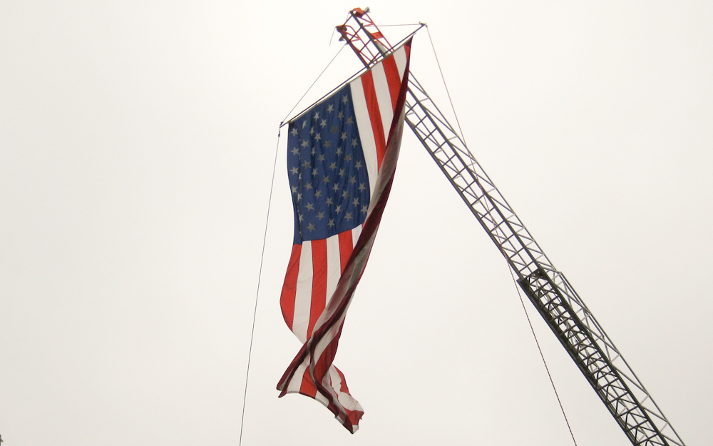 American flag hanging from a crane.